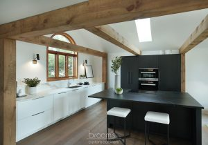 Courtright black and white painted minimal kitchen with wood beams 02