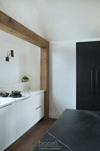 Courtright black and white painted minimal kitchen with wood beams 09