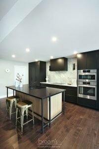 Faircloth black painted cabinets with natural wood and industrial island 05